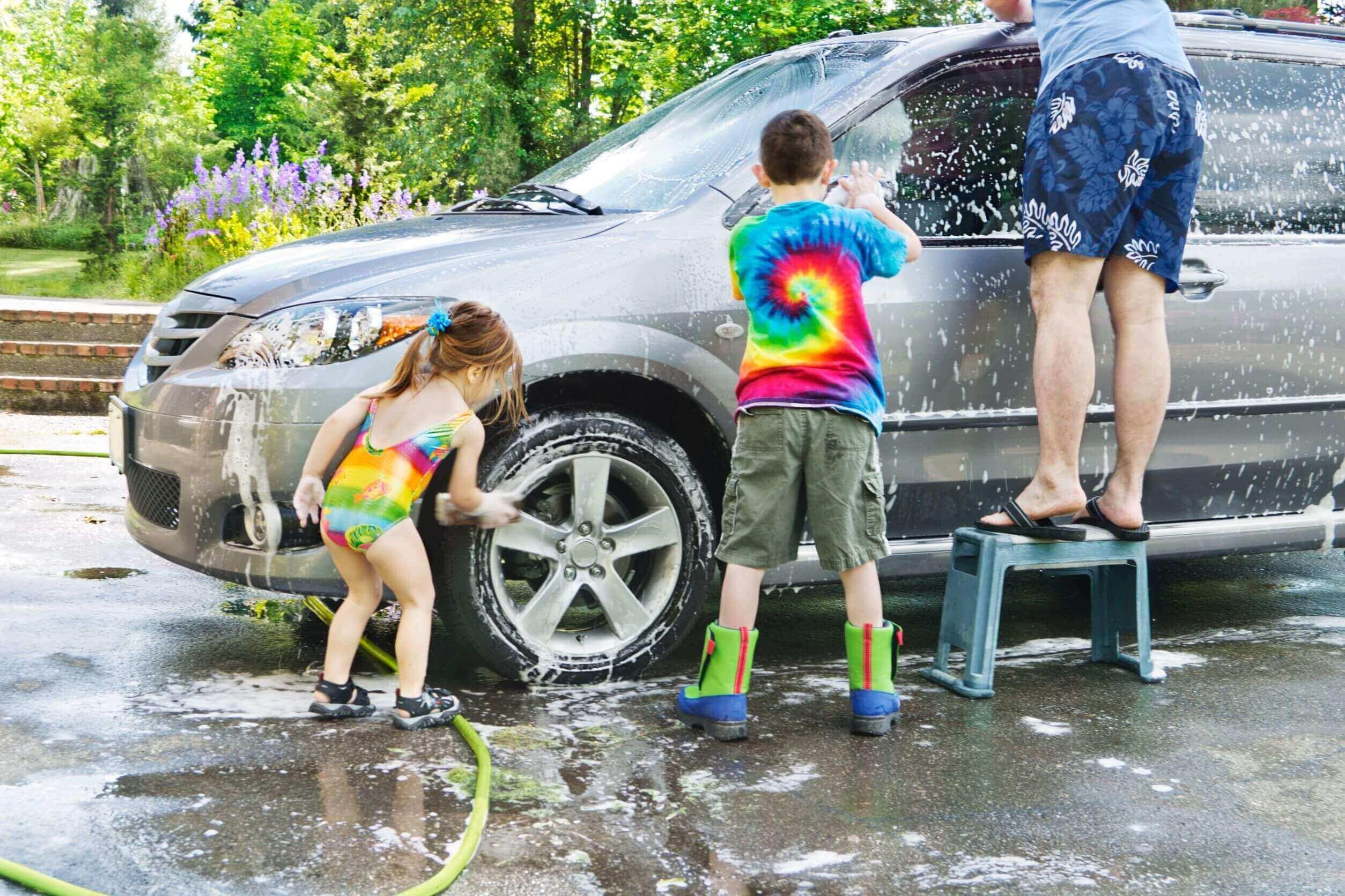 Kinder und Mann waschen Auto